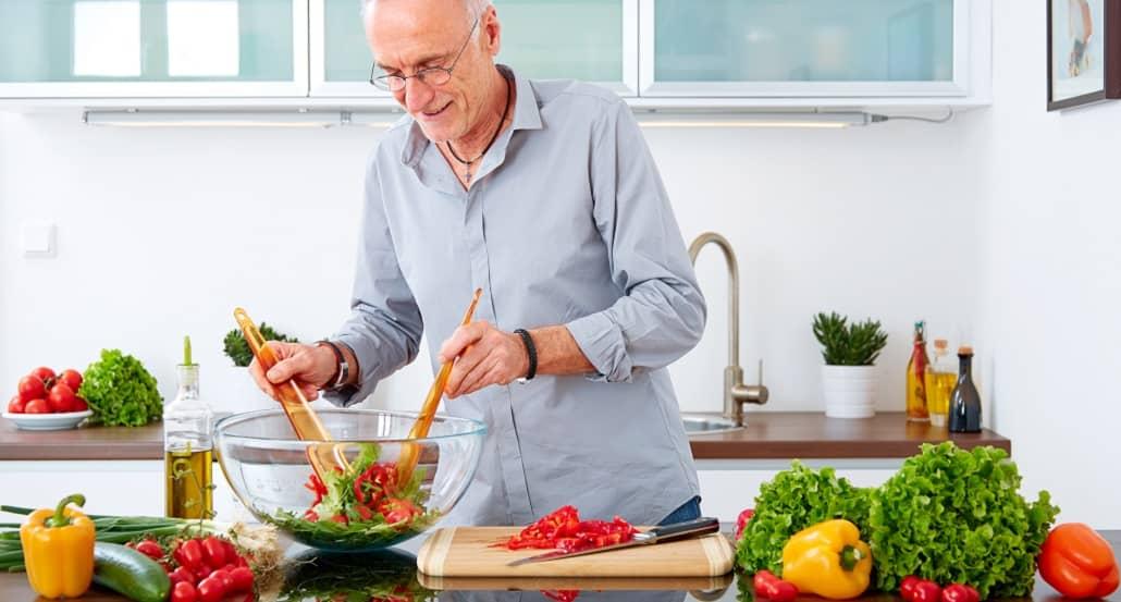 Ernährung ab 50+ - Mann bereitet einen Salat zu