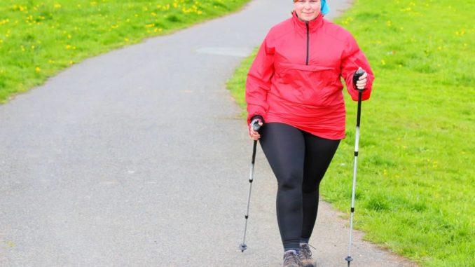 Übergewichtige Frau mit Nordic Walking Schuhen