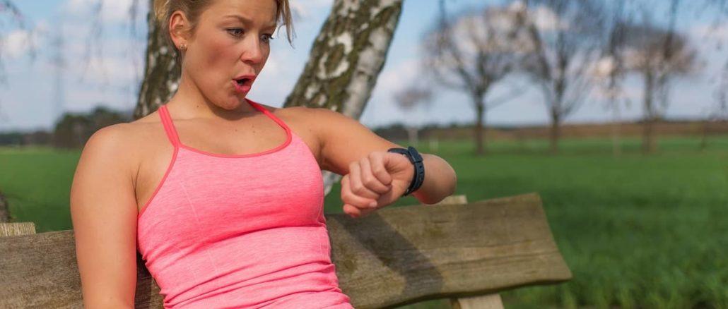 Frau schaut auf ihren Pulsmesser beim Nordic Walking